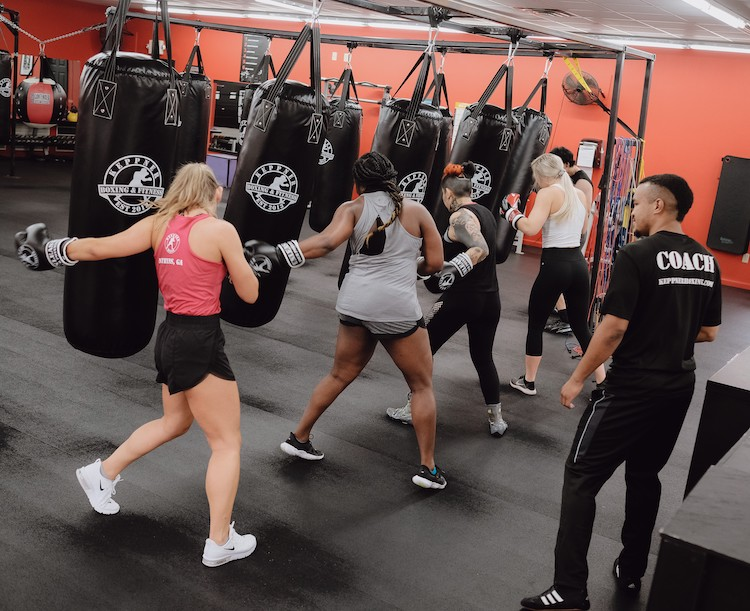 many students punching heavy bags in a cardio fitness boxing class