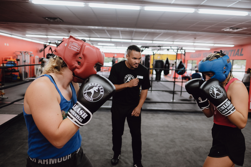 two students and coach practicing contact boxing
